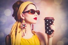 Kvinna i gul kläder med kaffe fotografering för bildbyråer