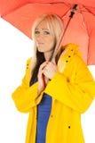 Kvinna i gult regnlag under det ledsna röda paraplyet fotografering för bildbyråer