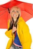 Kvinna i gult regnlag under det lyckliga röda paraplyet royaltyfria foton