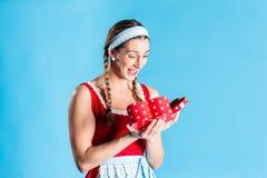 Kvinna i gåva för dirndlklänningöppning Royaltyfria Bilder