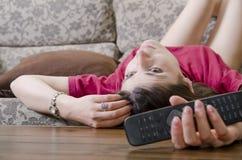 Kvinna i hållande ögonen på tv för soffa Arkivbild