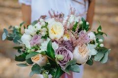 Kvinna i hållande bukett för vit klänning av blommor i skogbruden fru bröllop Royaltyfri Fotografi
