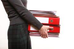 Den kvinnliga kontorsarbetaren som bär en bunt av, sparar Arkivbilder