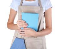 Kvinna i hållande kokbok för förkläde på vit bakgrund arkivfoto