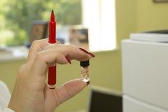 Kvinna i hållande liten medicinflaska för laboratorium Fotografering för Bildbyråer