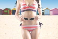 Kvinna i hållande solglasögon för swimwear royaltyfri fotografi