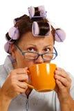 Kvinna i hårrullar som dricker kaffe i morgonen Arkivbilder