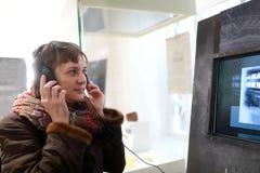 Kvinna i hörlurar som håller ögonen på film arkivfoton