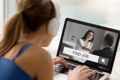 Kvinna i hörlurar som ser försöka att finna jobb direktanslutet royaltyfri foto
