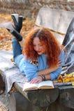 Kvinna i höstparken att ligga på en bänk med skyler och att läsa en bok höstbakgrundscloseupen colors orange red för murgrönaleaf arkivfoton