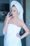 Kvinna i handduk som dricker vin royaltyfri foto