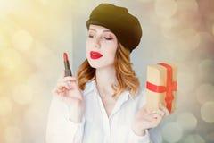 Kvinna i hatt med läppstift- och julgåvaasken Arkivfoto
