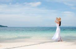 Kvinna i hatt på shoreline på den tropiska stranden Royaltyfri Fotografi