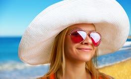 Kvinna i hatt på stranden arkivfoto