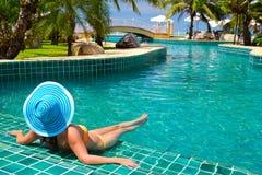 Kvinna i hatt som kopplar av på den tropiska simbassängen Royaltyfria Bilder