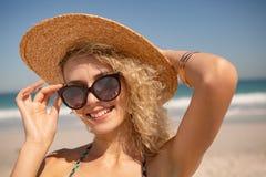 Kvinna i hatten och solglasögon som ser kameran på stranden arkivfoton