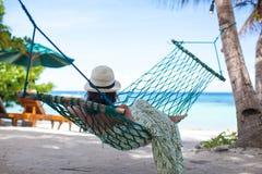 Kvinna i hatten som ligger i hängmatta i träds skugga på arkivfoto