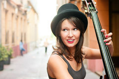 Kvinna i hatten som spelar basfiolen på gatan Arkivbilder