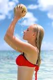 Kvinna i havet med kokosnöten som som dryper Arkivfoto