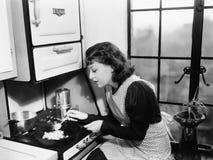 Kvinna i hennes kök som förbereder mat på ugnen (alla visade personer inte är längre uppehälle, och inget gods finns Leverantörwa Arkivfoton