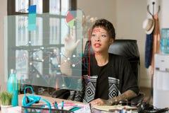 Kvinna i hennes kontor som tar fram information från en futuristiska Fina Royaltyfri Foto