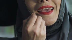Kvinna i hijab som offentligt applicerar röd läppstift, förbud på ljusa ställen för makeup stock video