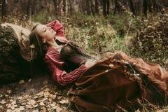 Kvinna i historisk klänning som vilar i höstskog Arkivfoto