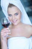 Kvinna i hållande exponeringsglas för vit badlakan av vin Fotografering för Bildbyråer