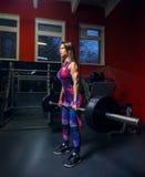 Kvinna i idrottshallen - deadlift med skivstången Arkivfoton