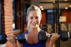 Kvinna i idrottshalllyftande handvikter Royaltyfri Fotografi