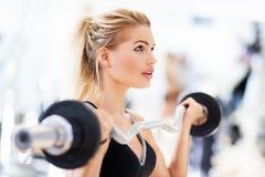 Kvinna i idrottshalllyftande vikter Arkivfoto