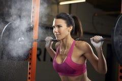 Kvinna i idrottshalllyftande vikter på skivstång Fotografering för Bildbyråer