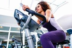 Kvinna i idrottshallsnurr på konditioncykeln royaltyfria foton