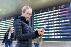 Kvinna i information om kontrollerande flyg för internationell flygplats på den smarta telefonen app Royaltyfri Bild