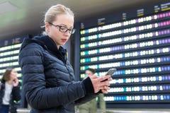 Kvinna i information om kontrollerande flyg för internationell flygplats på den smarta telefonen app Arkivbild