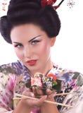 Kvinna i japansk kimono med pinnar och sushirulle Royaltyfri Fotografi