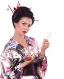 Kvinna i japansk kimono med pinnar och sushirulle Royaltyfria Bilder