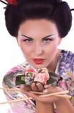 Kvinna i japansk kimono med pinnar och sushirulle Arkivfoto