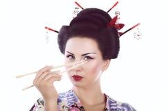 Kvinna i japansk kimono med pinnar och sushirulle Royaltyfri Foto