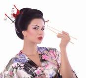 Kvinna i japansk kimono med pinnar och sushirulle Arkivfoton