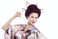 Kvinna i japansk kimono med pinnar och sushirulle Arkivbilder