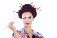 Kvinna i japansk kimono med pinnar och sushirulle Royaltyfri Bild