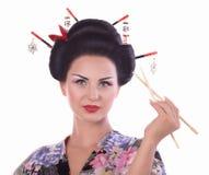 Kvinna i japansk kimono med pinnar och sushirulle Royaltyfria Foton