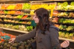 Kvinna i jordbruksprodukteravsnittet av en livsmedelsbutik arkivbild