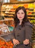 Kvinna i jordbruksprodukteravsnittet av en livsmedelsbutik arkivfoton