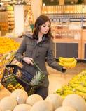 Kvinna i jordbruksprodukteravsnittet av en livsmedelsbutik royaltyfria foton