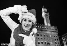 Kvinna i julhatt i Florence, Italien som inramar med händer Arkivfoton