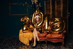 Kvinna i julhatt med guld- ballonger Royaltyfria Foton