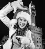 Kvinna i julhatt nära Palazzo Vecchio som inramar med händer Arkivfoton