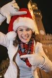 Kvinna i julhatt nära Palazzo Vecchio som inramar med händer Royaltyfria Foton